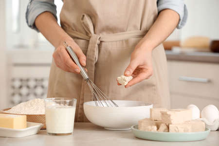 Woman adding compressed yeast for preparing dough at table indoors, closeup