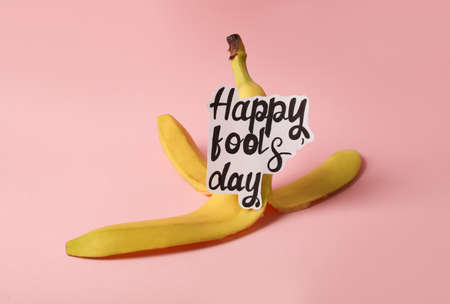 Banana peel with words Happy Fool's Day on pink background