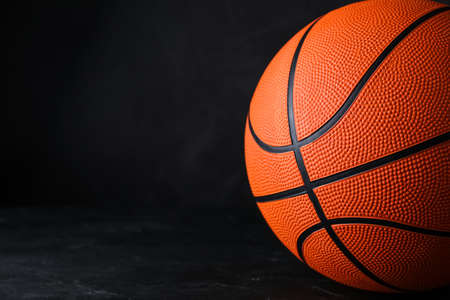 Orange ball on black background, space for text. Basketball equipment