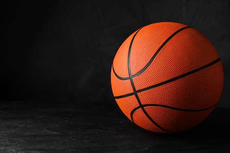 Orange ball on black background, space for text. Basketball equipment Stock fotó
