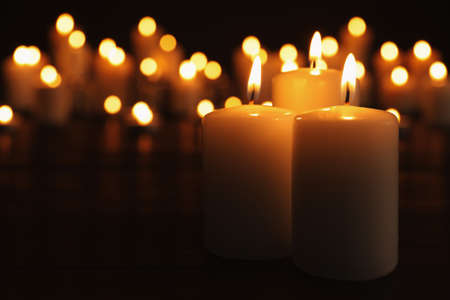 Burning candles on dark table, space for text. Memory day