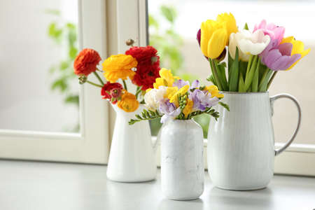 Different beautiful spring flowers on window sill Imagens