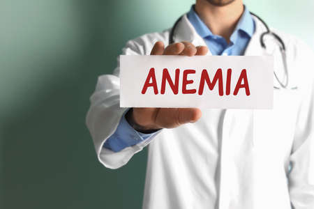 Doctor holding sign with word ANEMIA on color background, closeup Stock Photo