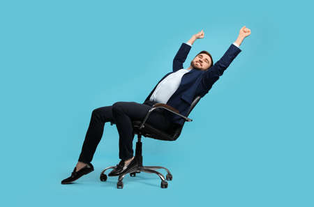 Young businessman stretching in comfortable office chair on turquoise background Banque d'images