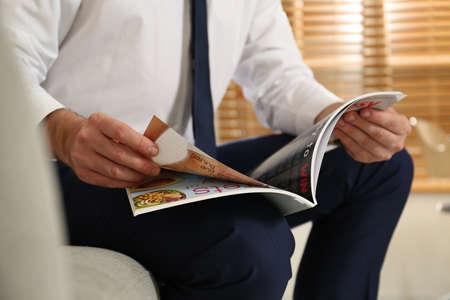 Businessman reading modern magazine at home, closeup