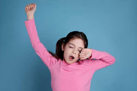 Sleepy little girl yawning on light blue background