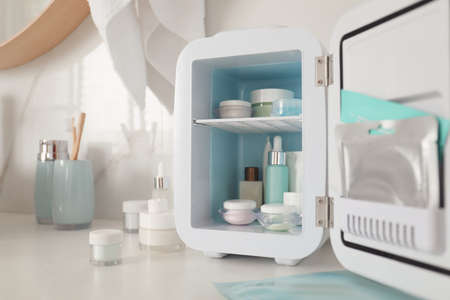 Cosmetics refrigerator and skin care products on white table indoors, closeup