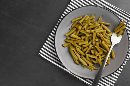 Canned green beans served on black table, top view