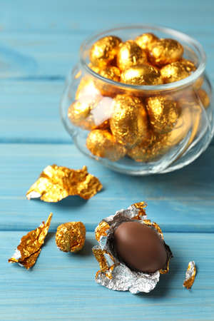 Chocolate eggs wrapped in golden foil on light blue wooden table