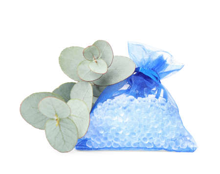 Scented sachet with aroma beads and eucalyptus branches on white background