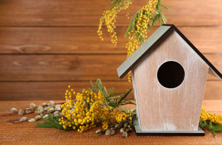 Stylish bird house and fresh flowers on wooden table. Space for text