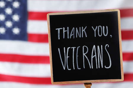 Sign with phrase Thank You, Veterans against American flag, closeup. Memorial Day