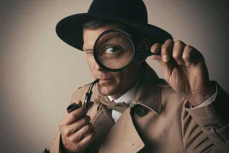 Male detective with smoking pipe looking through magnifying glass on beige background Stock Photo