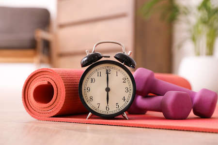Alarm clock, yoga mat and dumbbells on wooden floor indoors. Morning exercise