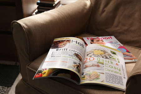 Different lifestyle magazines on comfortable armchair indoors