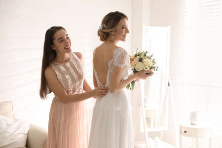 Young woman helping bride to put on wedding dress in room