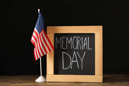Blackboard with phrase Memorial Day and American flag on wooden table