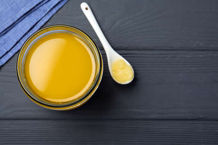 Glass jar and spoon of Ghee butter on grey wooden table, flat lay. Space for text Stock Photo