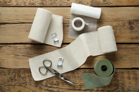 Medical bandage rolls, sticking plaster and scissors on wooden background, flat lay
