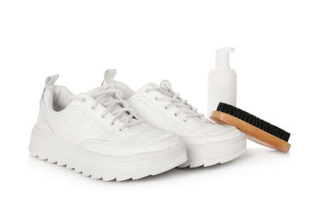 Stylish footwear and shoe care accessories on white background