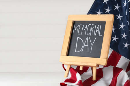 Blackboard with phrase Memorial Day and American flag on white wooden table, space for text