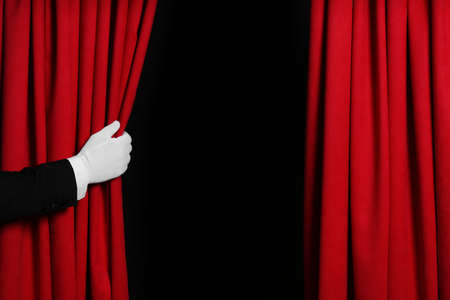 Person opening red front curtains on black background, closeup. Space for text Archivio Fotografico