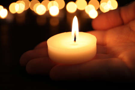 Woman with burning candle in darkness, closeup. Memory day