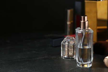 Bottle of perfume on dark table. Space for text Stock Photo