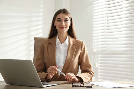 Portrait of beautiful young businesswoman with laptop at table in office