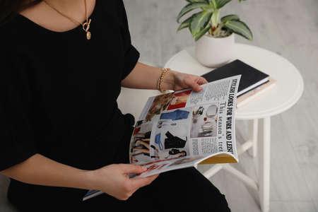 Young woman reading fashion magazine indoors, closeup