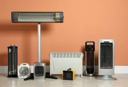 Different electric heaters near orange wall indoors