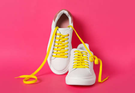 Pair of stylish shoes with yellow laces on pink background