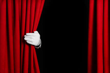 Person opening red front curtains on black background, closeup. Space for text