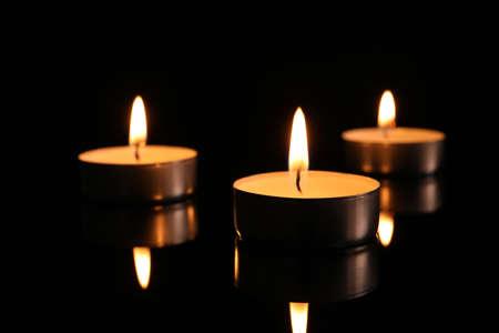 Burning candles on dark background. Memory day