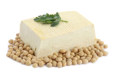Piece of delicious tofu with parsley and soy on white background