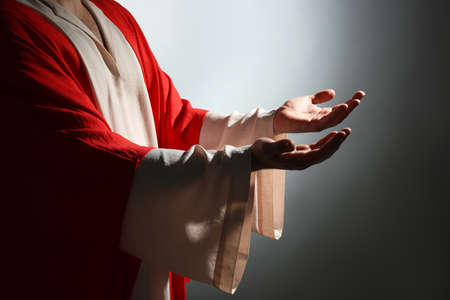 Jesus Christ reaching out his hands on grey background, closeup