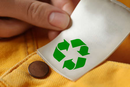 Woman showing clothing label with recycling symbol on yellow jeans, closeup Stock Photo