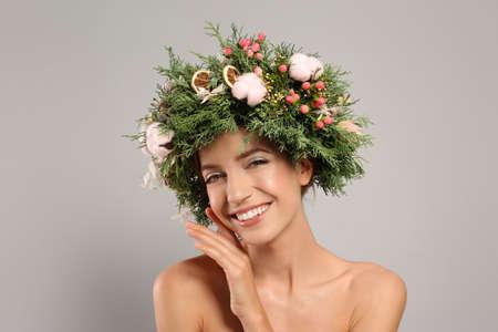 Happy young woman wearing wreath on grey background 版權商用圖片