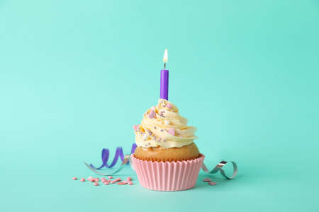 Birthday cupcake with burning candle and sprinkles on turquoise background