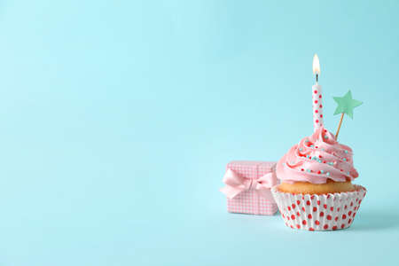 Birthday cupcake with burning candle, gift box and topper on light blue background. Space for text
