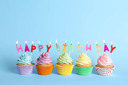Birthday cupcakes with burning candles on light blue background