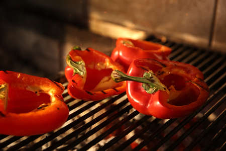 Cooking delicious fresh bell peppers on grilling grate in oven, closeup