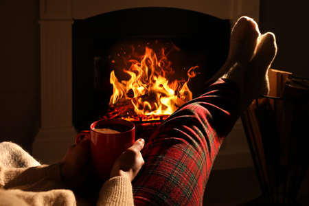 Woman in knitted socks with cup of drink near fireplace at home, closeup