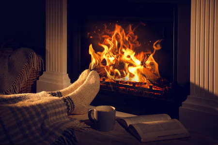 Woman with cup of drink and book near fireplace at home, closeup