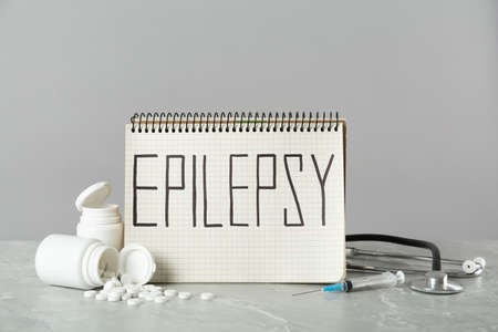 Notebook with word Epilepsy, stethoscope, pills and syringe on gray marble table