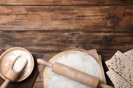 Matzos and raw dough on wooden table, flat lay. Space for text