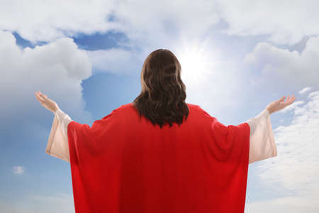 Jesus Christ with outstretched arms against blue sky, back view
