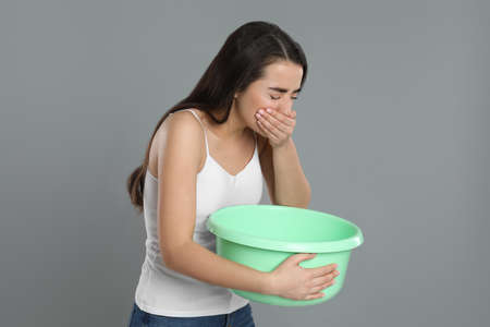 Young woman with basin suffering from nausea on grey background. Food poisoning