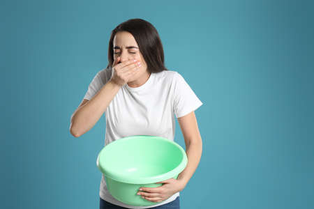 Young woman with basin suffering from nausea on light blue background. Food poisoning