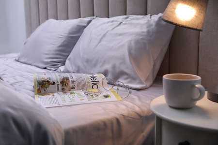 Magazine on bed with soft silky bedclothes in room Stock Photo